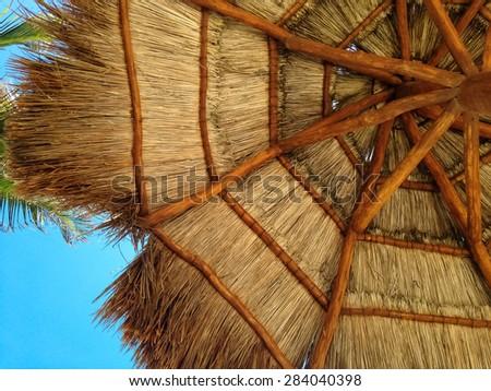Looking up at a beach umbrella on a sunny beach. - stock photo