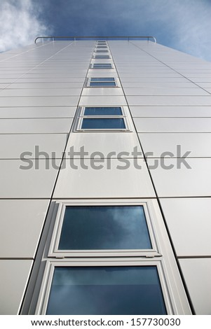 Looking up at a modern white building against a blue sky
