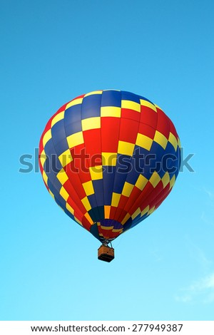 Looking up at a red, blue, and yellow hot air balloon as it soars and flies in the clear blue sky.
