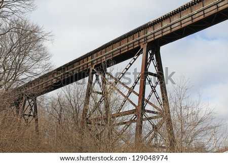 Looking up at an old but still used railroad bridge and trestle - stock photo
