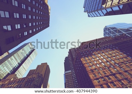 Looking up at buildings in Manhattan skyscrapers in vintage style, New York City - stock photo