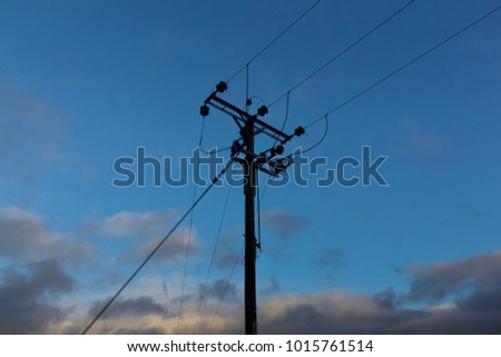 Looking up at domestic overhead power cables against a blue sky
