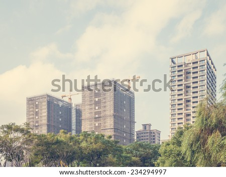 Looking Up at High Rise Buildings Under Construction as part of Urban Skyline with Tree Tops