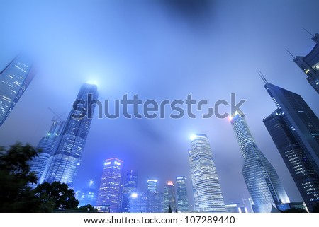 Looking up at the modern office buildings at night in Shanghai - stock photo