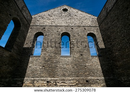 Looking up at the towering stone wall of an ancient church ruins with three gothic windows. - stock photo