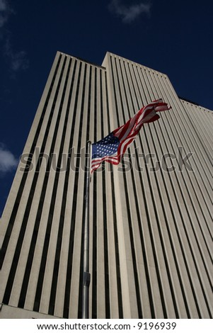 Looking up at white skyscraper with American Flag