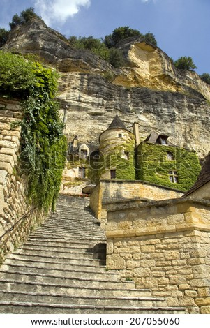Looking up steps towards a turret and cliffs in a French hillside town