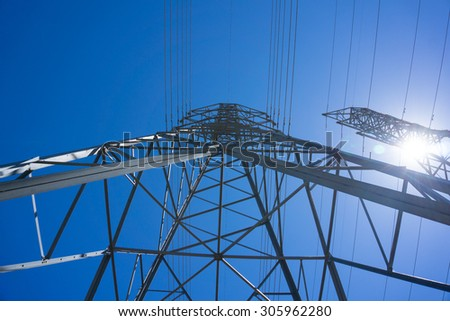 Looking up the electric tower structure holding wires. - stock photo