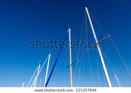 Looking up the mainmasts and blue sky background, around port.