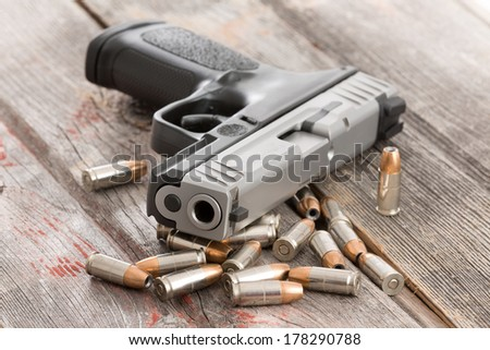 Looking up the muzzle of a handgun surrounded by scattered bullets and ammunition lying on old rustic wooden boards conceptual of violence, killing, crime and burglary - stock photo