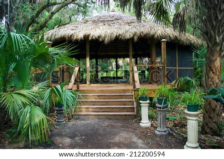 Looking up the path to a thatched roofed screened building in park in estero florida. - stock photo