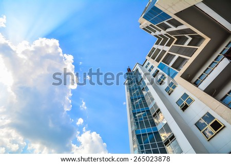 Looking up the sky by side of the building. blue sky with clouds and sunbeam - stock photo
