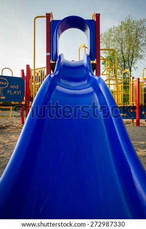 Looking up toward the top of a blue plastic slide at a children's playground.