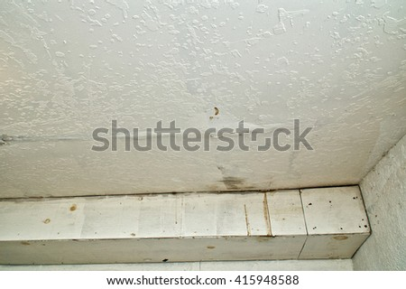 Looking up towards ceiling at water damage, stained and bubbled up paint from  leakage caused by rain. - stock photo