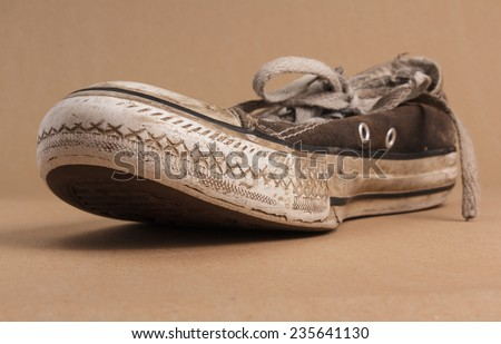 Looking up under the sole of an old dirty sneaker - stock photo