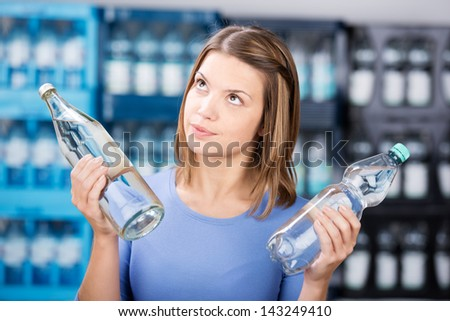 Looking up woman holding two glass bottle with water - stock photo