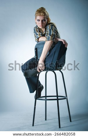 Looking young girl in the studio sitting on a bar stool - stock photo