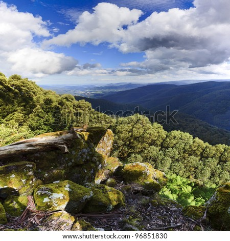 lookout high in Barrington tops mountains view at green eucalyptus valley undre blue sky with clouds - stock photo