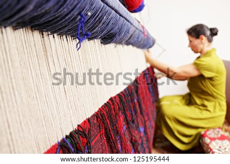 Loom for hand weaving carpet with woman working at backstage - stock photo