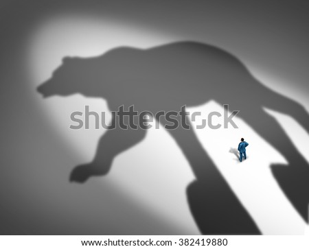 Looming financial crisis and slumping stock market business concept as a businessman standing in front of the cast shadow of a bear as a loss and price decline metaphor. - stock photo