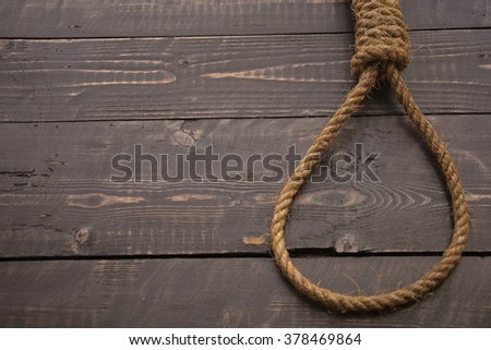 Loop hempen rope on a dark wood tables background. Classic loop knot on grunge wooden background - stock photo