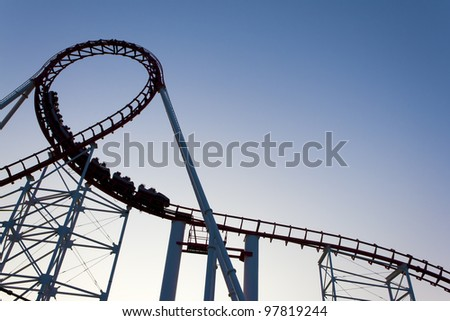 Loop of a roller coaster back lit by the sunset. - stock photo