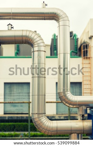 Loop steam pipeline on cooling tower background.