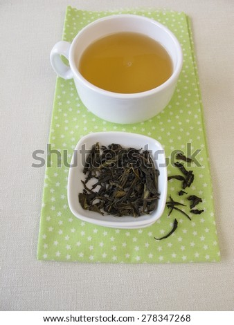 Loose ceylon royal silver white tea and cup of tea - stock photo