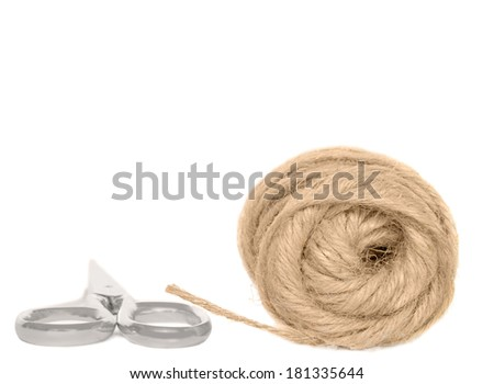 Loose coil of hemp rope and closed metal shears. Scissors handle close up with strand of twine. Isolated, horizontal photo. Room for text, copy space.  - stock photo