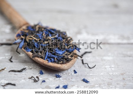Loose Earl Grey tea leaves on a vintage wooden spoon and table - stock photo