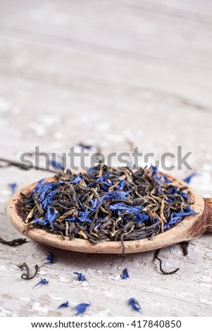 Loose Earl Grey tea leaves on a vintage wooden spoon and table with space for text - stock photo