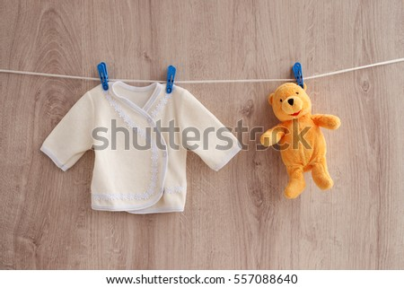 Loose jackets hanging on a rope. Fleece loose jackets with delicate lace and teddy bear hanging on clothespins on a rope. Clothing for children dries after washing. Loose jackets for baby beige.