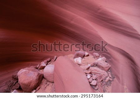 Loose rocks and sand that move with flowing water to smooth and carve out the walls of a sandstone canyon in Arizona. - stock photo