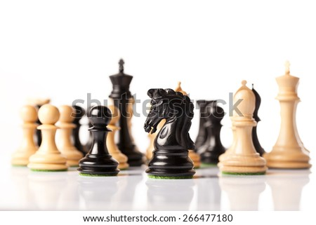 Loose standing black and white chess pieces on a table  - stock photo