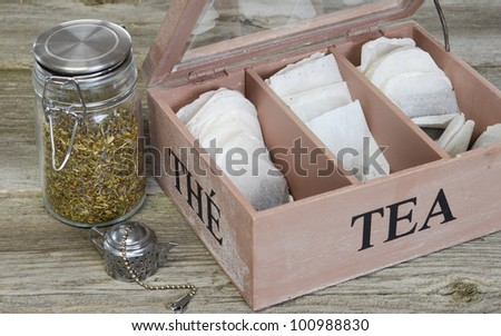 Loose tea in a spring top container and tea bags in a lettered box. - stock photo