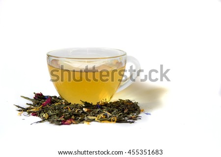Loose tea is near the cup of tea on a white background isolated.