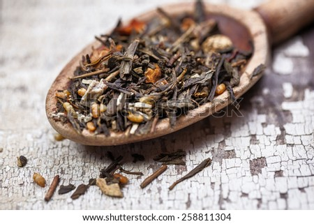 Loose tea leaves on a vintage wooden spoon and table - stock photo