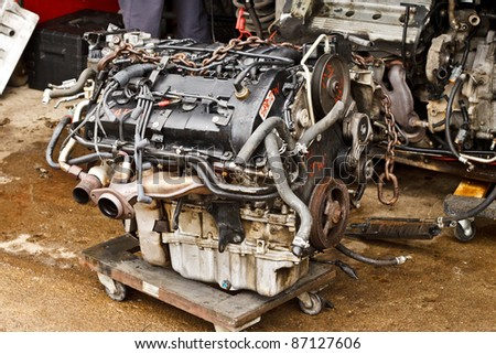 Loose vehicle engine at repair shop on wheeled cart - stock photo