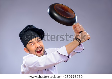 Loosing his temper. Closeup portrait of handsome angry cook striking somebody with his frying pan while standing over grey background with copy space - stock photo