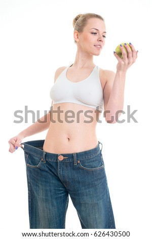 Loosing weight woman in big jeans showing thumb up. Slim body care girl posing in studio with green apple.