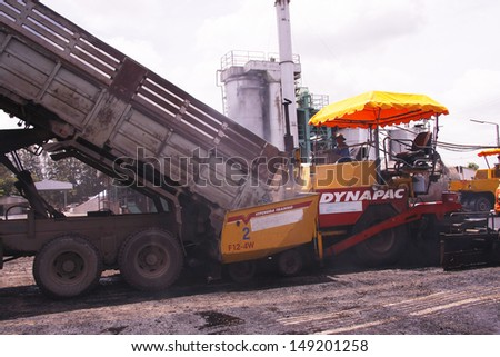 LOP BURI,THAILAND - AUGUST 3 :Workers operating asphalt paver machine and heavy machinery during repairs road under the  program repairs road in asphalt plant on August 3,2013 in Lop Buri,Thailand.