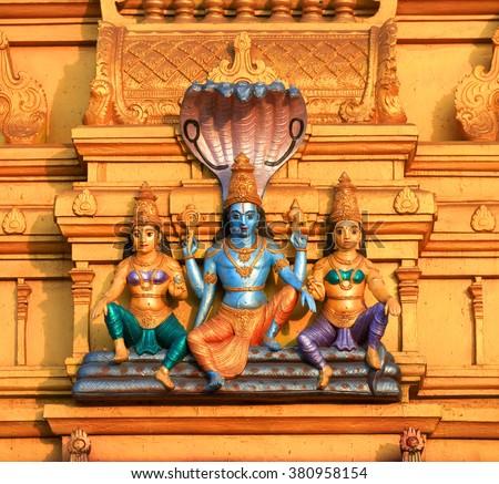 Lord Vishnu statue on exterior architecture of hindu temple - stock photo
