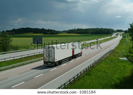lorry driving late in the evening, on long stretch of highway - stock photo