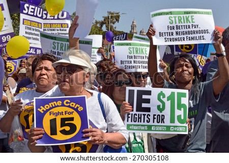 LOS ANGELES, CA   APRIL 15, 2015: Protestors hold signs advocating raising the minimum wage at during a rally in Los Angeles on April 15, 2015. - stock photo