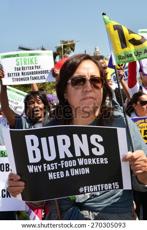 LOS ANGELES, CA   APRIL 15, 2015: Protestors hold signs advocating raising the minimum wage for fast food workers during a demonstration in Los Angeles on April 15, 2015.