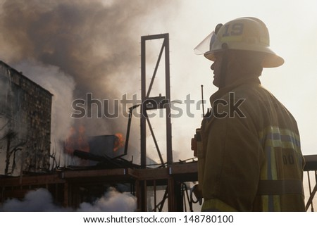 LOS ANGELES, CA - CIRCA 1990's: Firefighter with smoldering building in background in Los Angeles, CA