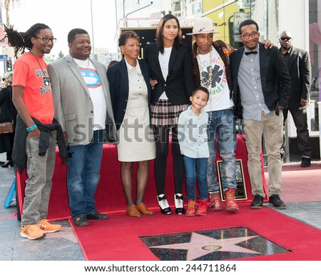 LOS ANGELES, CA - DECEMBER 4, 2014: Singer/songwriter Pharrell Williams with wife & son & family on Hollywood Boulevard where he was honored with the 2,537th star on the Hollywood Walk of Fame.  - stock photo