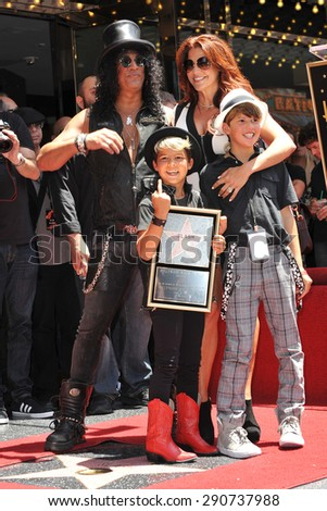 LOS ANGELES, CA - JULY 10, 2012: Rock guitarist Slash & sons & wife Perla Ferrar on Hollywood Blvd where he was honored with a star on the Hollywood Walk of Fame. - stock photo