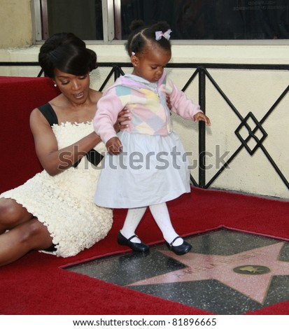 LOS ANGELES, CA - MAR 20: Actress Angela Bassett receives a star on the Hollywood Walk of Fame in Los Angeles, California on March 20, 2008. She poses with daughter Bronwyn Golden