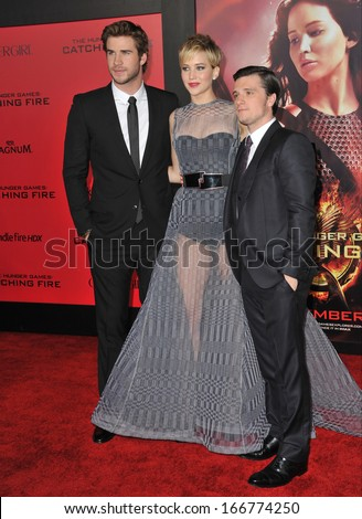 """LOS ANGELES, CA - NOVEMBER 18, 2013: Jennifer Lawrence with Liam Hemsworth (left) & Josh Hutcherson at the US premiere of their movie """"The Hunger Games: Catching Fire"""" at the Nokia Theatre LA Live.  - stock photo"""